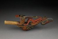 Rattle in shape of a raven, carrying on its back a reclining figure with bent knees and extended tongue; human figure is joined by his tongue to a frog, which is held in the beak of a kingfisher bird, whose head is depicted (without a body) and located closest to the handle of the rattle. The underside of the rattle (the raven's belly) has the abstracted features of a human face.