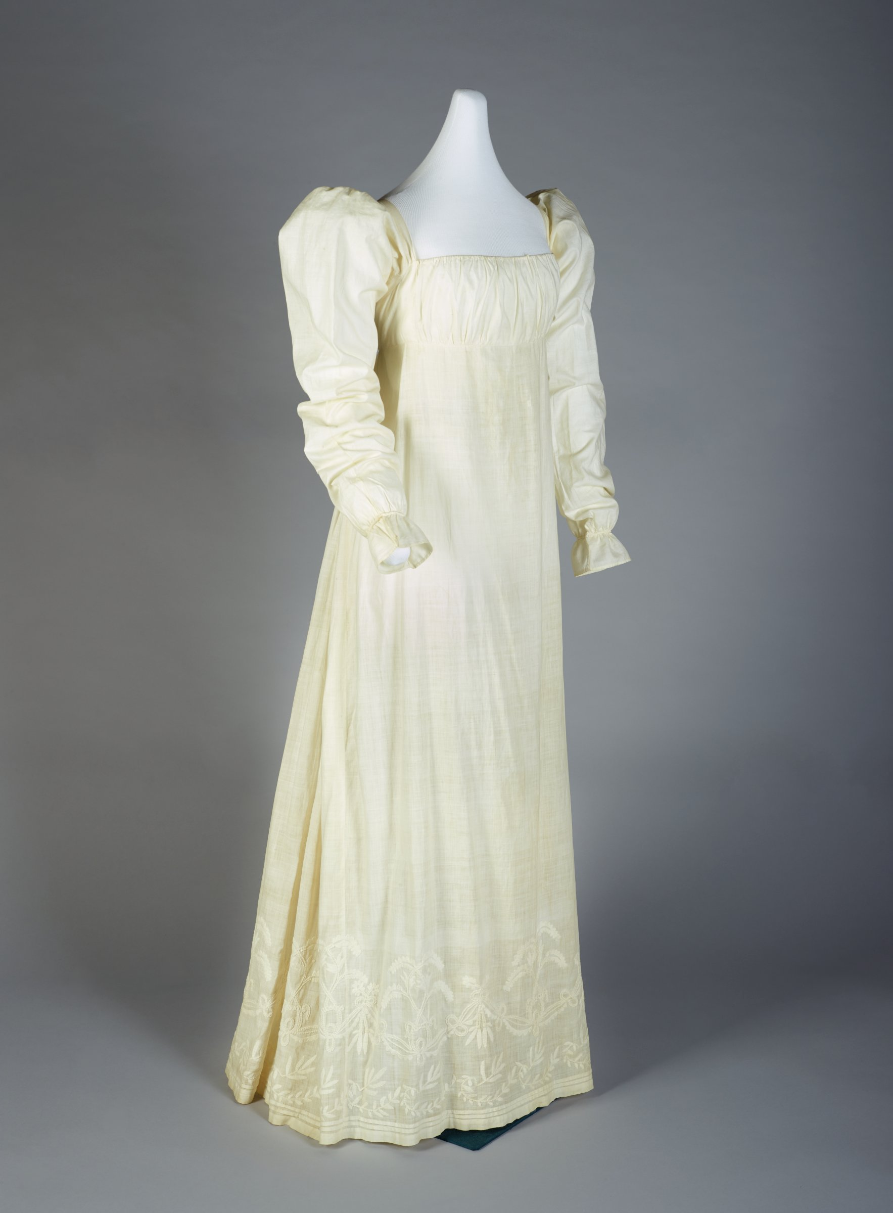 Simple white cotton muslin chemise dress with long sleeves, gathered neck and Empire waist with drawstring gathers and sash, with decorative floral embroidery in white consisting of vines and bows, in long and short stitch at hem, slightly trained.