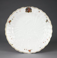 """Large round charger with a wavy edge and molded in relief with in the center two swans with their heads together swimming amongst the rushes, which are filled with a heron, fish and shells, above them a second heron in flight; in the background is a radial sunburst that extends to the rim of the plate, which is decorated with a finely gilt spearhead border and scattered flower sprays in Kakiemon colors (""""indianische Blumen""""); at the top of the plate is the coat of arms of the Brühl and Kollowrat families."""
