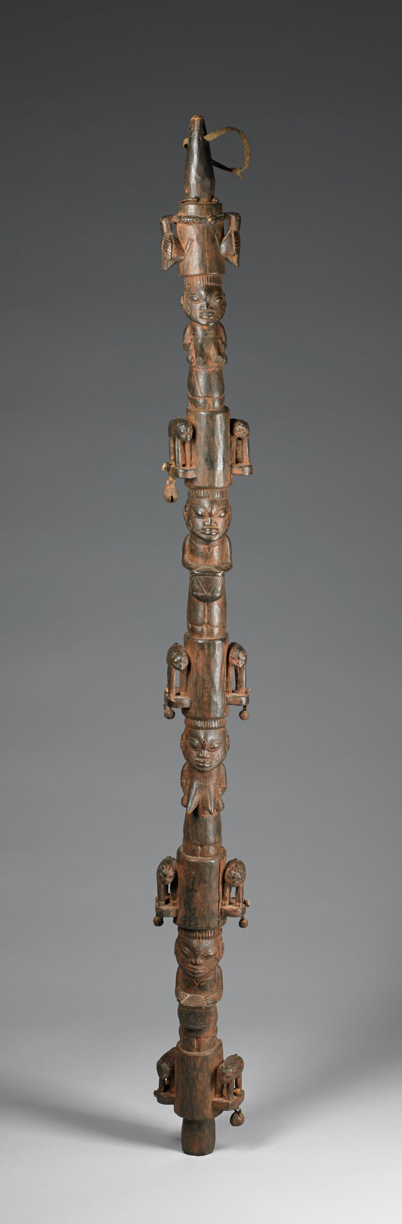 One of four staffs used to deliniate an area around a royal when he appears in public.  Decorated with kneeling female figures with hands on breasts, alternated with knelling male drummers, at top birds and a python, below figures are quadrupeds, possibly goats, symbols of wealth.