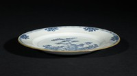 Blue and white plate, interior painted with a central garden scene of rock, bamboo, peony, etc. Rim occupied by a diaper band interspersed with six profile lotus. Edge of rim highlighted in iron brown. Underside of plate is plain. Glazed entirely except for footring, exposing a buff paste.
