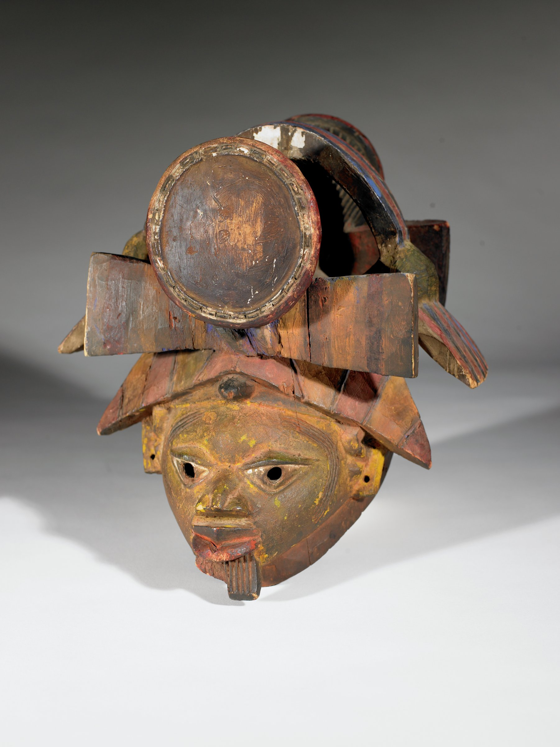 Mask/headdress composed of male face with beard and pierced eyes, topped by head-ware which includes sculpted drum resting on framework, held in place by sculpted fabric tie.