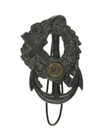 Cast-iron key hook in the form of an anchor decorated with a floral wreath and cross, in the center a small medallion with a rosette.