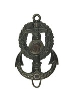 Cast-iron key hook in the form of an anchor decorated with a leafy wreath, in the center a medallion with the portrait head of a male, probably Neptune, in profile left, the back mounted with a hook.