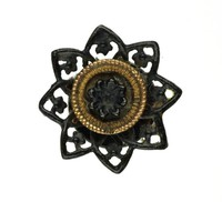 Small cast-iron cuff link, or button, star-shaped with eight points pierced with foliate motifs, the central medallion with a rosette set in gold.