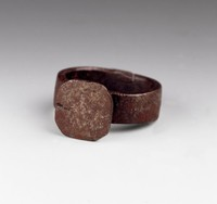 Large ring made from a horseshoe nail, the wide, hinged band supports a plate with truncated edges, originally mounted with a stone.