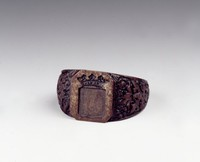 Cast-iron signet ring, the thick, tapered band with relief decoration of birds and foliage, the square plate with a coat of arms and crown.
