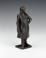 Small statuette of Johann Wolfgang von Goethe standing in full figure on small, flat, square base, wearing trousers and long, buttoned frock coat, open at the neck and with scarf, his left hand on his hip, his right hand holding a book.