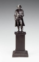 Cast-iron statuette of Napoleon I Bonaparte standing with his left leg casually bent, his left hand in his coat and his right hand at his side, wearing the uniform of a French general with bicorn hat and long open coat, a sword at his left hip, the statuette resting on a tall, square plinth with rectangular base decorated with anthemion motifs.