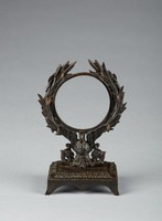 On a four-footed, square base with arched skirt and a border of palmette motifs, a stand in the form of a laurel wreath supported by a swan with outstretched wings and stylized floral elements, with three prongs on each side for jewelry.