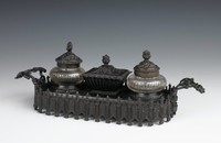 Long rectangular inkwell of cast iron, the base enclosed by a row of alternating Gothic-style ornaments—a fluted column with a leafy element on top and a shield with Gothic tracery—on either side an outwardly scrolling handle comprised of foliate motifs, the central inkwell with on either side two bulbous cut glass containers with cast iron covers that are decorated in a stylized organic pattern, the finials in the form of stylized leaves, in the middle a cast iron container with tapered, fluted sides and a flat cover similar to the other two and decorated with stylized organic motifs, with same leaf finial.