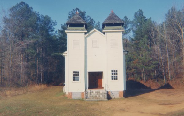 A small white church sits at the center of the composition. The church stands in a flat clearing of low grass and bare dirt. Behind the church are trees. The sun brightly lights the church.