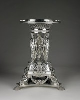 Tall, elegant silver centerpiece resting on a flat, triangular base with concave sides and guilloche border, mounted on three delicately chased shell feet, the lower body of the centerpiece likewise of triangular form with two bands of guilloche molding and the cast and applied arms of the Earls of Coventry on all three long sides separated by individual molded scroll motifs on the short sides, supported by three dolphins with looped tails between heavy swags of fruit and flowers; on each angle of the lower body stands a female figure of caryatid type sculptured in the round and clad in a classically draped gown and sandals, facing outward, the figures hold in each hand the wand, or scepter, of Dionysus, one surmounted by a pine cone and the other by ivy leaves and berries, so that they form a criss-cross pattern with the wands, which are crossed and tied near the middle with large bows, in the center of the figures is a large round medallion, and resting lightly on the heads of the figures is a circular stand decorated with a frieze of scrolling foliage and flowers below a large bowl of open basketwork rising to a double-plaited edge with a band of guilloche. A glass liner (now missing) originally fit into the bowl.