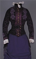 Velvet jacket and bustle with buttons down front, lace collar and sleeves, beaded flowers and fringe. Stays sewn in.