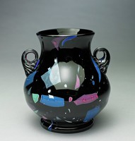 """Small black lead glass, footed vase with a globular shape and elongated neck, with two curved, fluted handles, inlaid with enamel glass in shades of pink, red, green, and blue; """"Lava"""" glass"""