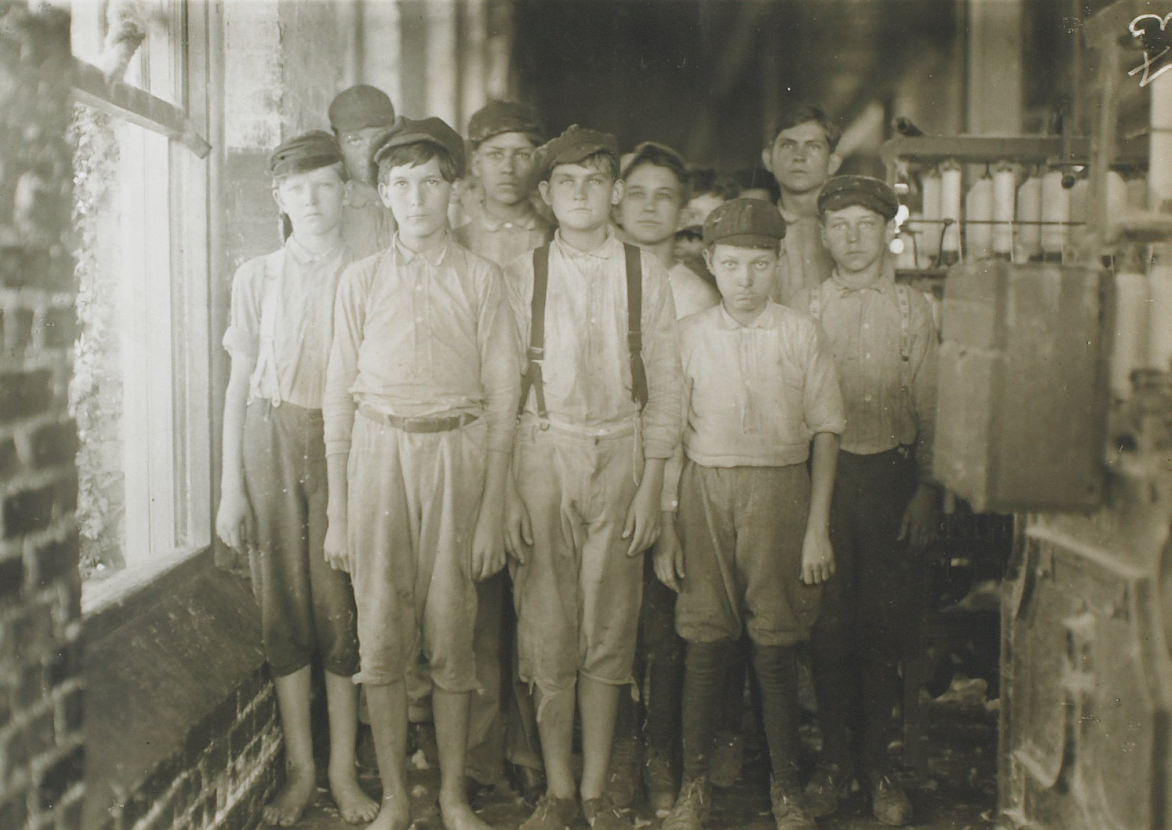 In this black and white photograph, a group of young men and boys stand in a mill or factory to the right of a brick wall and a brightly lit window. Nine people are clearly visible. To the right of the group of boys are machines displaying bobbins loaded with spooled thread.