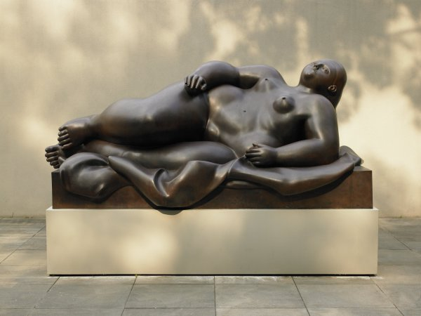 """The object is an oversized bronze sculpture of a reclining, longhaired female nude with an up-turned face. The figure rests on a fabric which drapes over a twelve-inch high base. The surface has a warm brown patina. The whole sculpture currently rests on base that raises it 21 inches off the ground. In this sculpture, Botero reinterpreted the odalisque, merging characteristics of primitive fertility goddesses with the voluptuous women of Rubens, Renoir, or Titian. Botero concentrates the heft in his figures at their center to attain the highest degree of volumetric expression and linear precision. His figures have been dubbed """"Boteromorphs."""" Botero's art reflect the culture of his native Medellín, where pre-Columbian aesthetic traditions intermingle with the lingering influence of medieval Spanish Catholicism. Botero has also absorbed the influences of Diego Rivera, Henri Matisse, and others."""