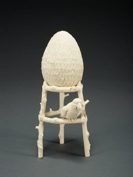 Unglazed porcelain sculpture in two parts: egg covered with feathers which sits on a stand that looks like a footstool made of twigs with a bird sitting on its middle rung.