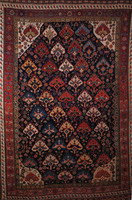 Qashqai rug (Persian), circa 1885, the midnight blue background with rust borders, with overall palmettes in diagonal rows of white, blue and rust; stylized chicken borders