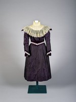 Irridescent purple dress with embroidered leaf design, slightly gathered sleeve at shoulder, falling straight o purple and ecru lace cuff (semi-fitted sleeves), velvet and lace at waistline, pleated at center front, softly gathered waist, lace and velvet decoration at yoke, mandarin style collar, bodice and skirt lined.