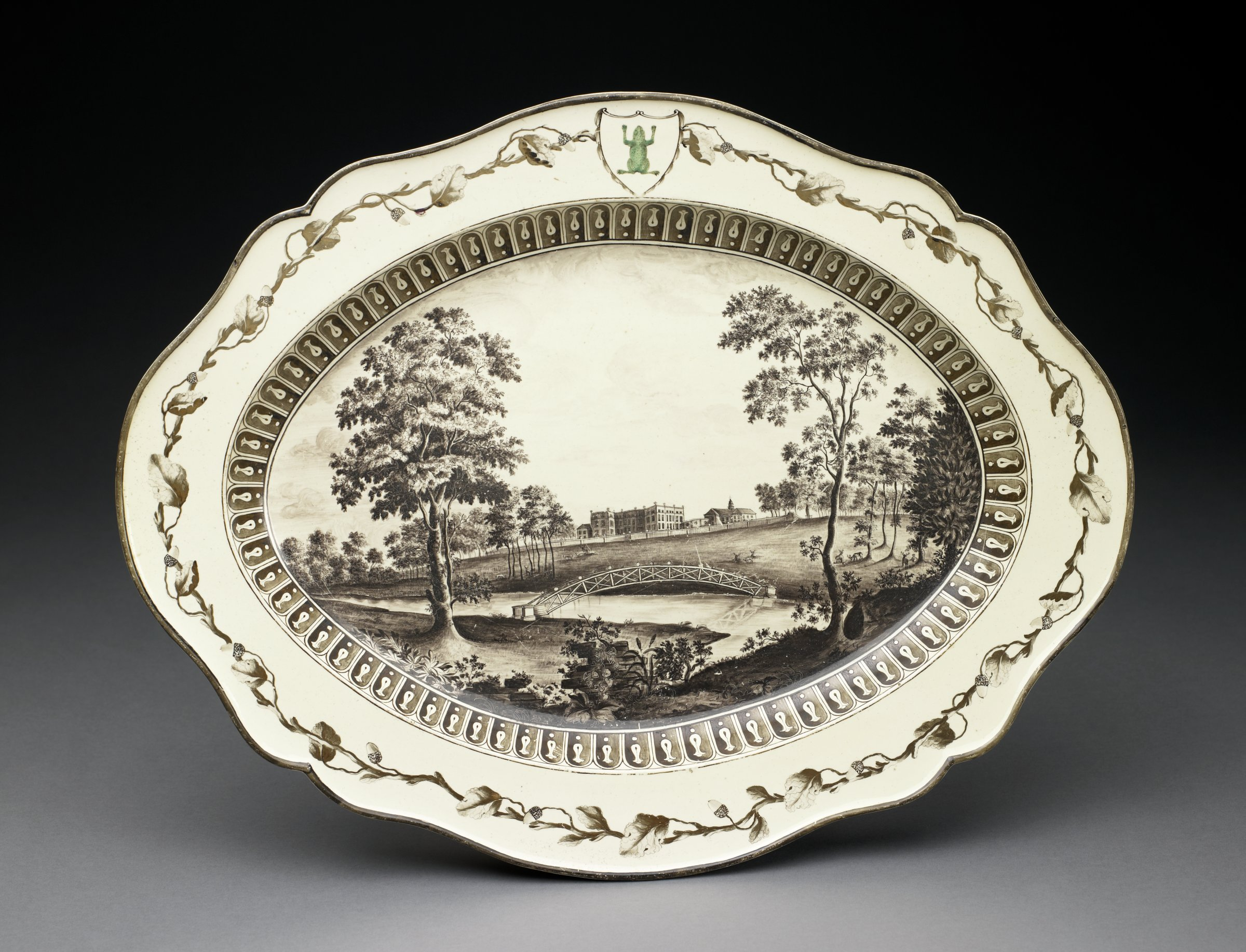 Large creamware platter of 'Catherine' shape, the center hand-painted in monochrome mulberry black with a view of Ditchley Park in Oxfordshire showing the house and stables in the background with the estate's park, a river, and a bridge between two trees in the foreground within a border of gadroons, the rim with a garland of oak leaves and acorns with the green frog crest within a cartouche at the top.
