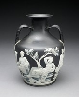 Copy of the Roman glass Portland Vase (now in the British Museum) in solid black jasper with white jasper relief decoration, the two-handled vase in the shape of an amphora, one side shows on the left the image of a nude male emerging from an architectural structure and grasping the arm of a recumbent, draped female figure holding a sea serpent, above her is a flying cupid holding his bow and arrows, to the right is a tree and a nude male figure resting his right leg on the stump, his chin in his right hand, which is resting on his knee; on the other side left is a draped male figure seated on a rocky structure next to a column, he looks over his shoulder to his left at a central figure, a draped, recumbent female, lying on the rocky base, looking slightly left and with her right arm reaching over her head, behind her and to the right is the figure of a draped seated male looking over his right shoulder at the central figure; underneath each handle is a bearded mask; the base with the image of a cloaked figure, head lowered, wearing a wrapped headdress, with right arm raised to face, in the background foliage; the white relief has been selectively shaded using a black jasper slip to give the impression of enhanced translucency.
