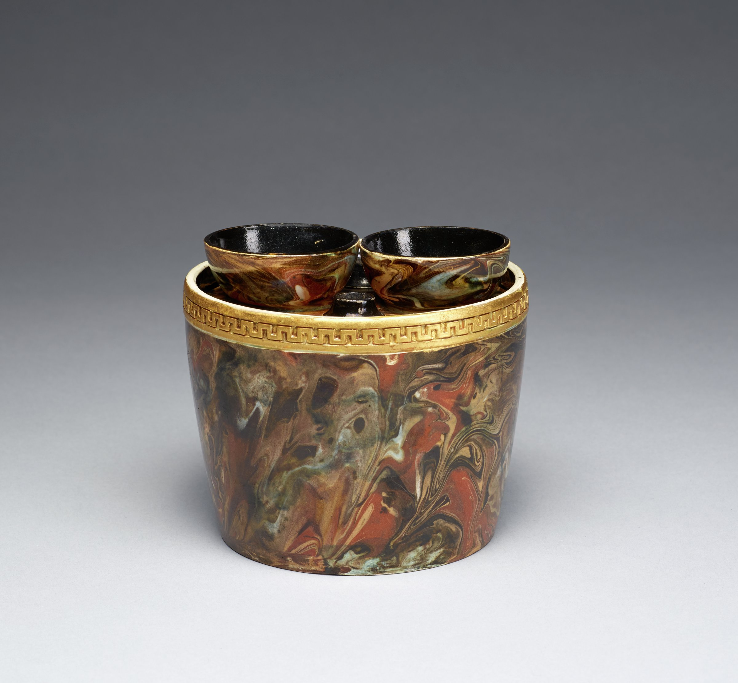 Small bulb pot of white stoneware covered with an opaque variegated agate glaze in shades of brown, beige, green and yellow, below the lip a band of gilded fret work, the fitted cover with two spouts to hold bulbs and two smaller air holes, both the interior of the pot and underside of the cover are glazed black.