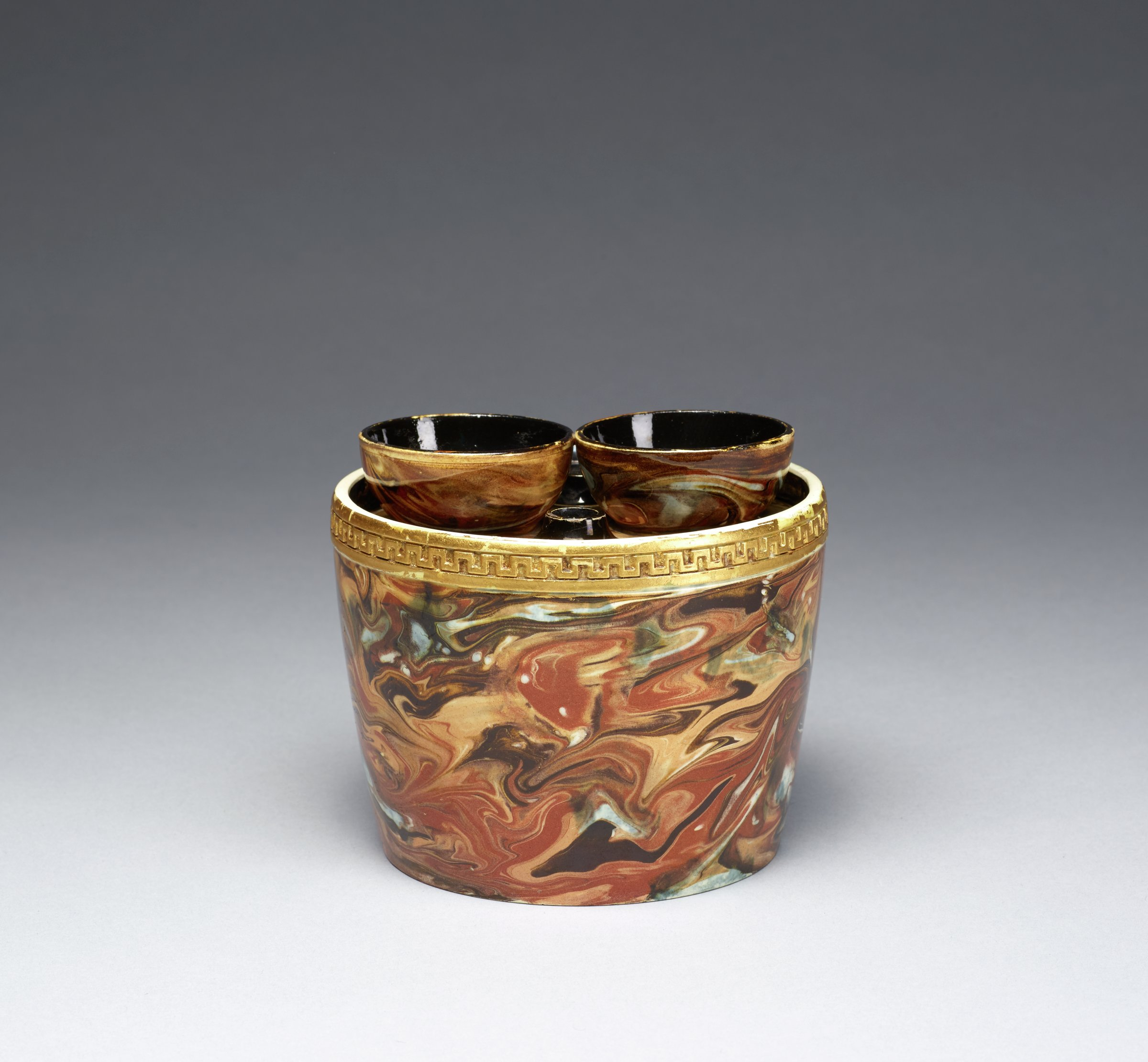 Small bulb pot of white stoneware covered with an opaque variegated agate glaze in shades of brown, beige and yellow, below the lip a band of gilded fret work, the fitted cover with two spouts to hold bulbs and two smaller air holes, both the interior of the pot and underside of the cover are glazed black.