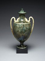 Urn-shaped covered vase (cover not original) of white stoneware resting on a small black basalt plinth, the body of the vase covered with an agate, or crystalline, glaze in shades of gray, browns and blues designed to resemble stone, the two ear-shaped handles left white and with traces of gilding, the handles terminate in masks of bearded tritons at the shoulder, the long neck with an extended lip.