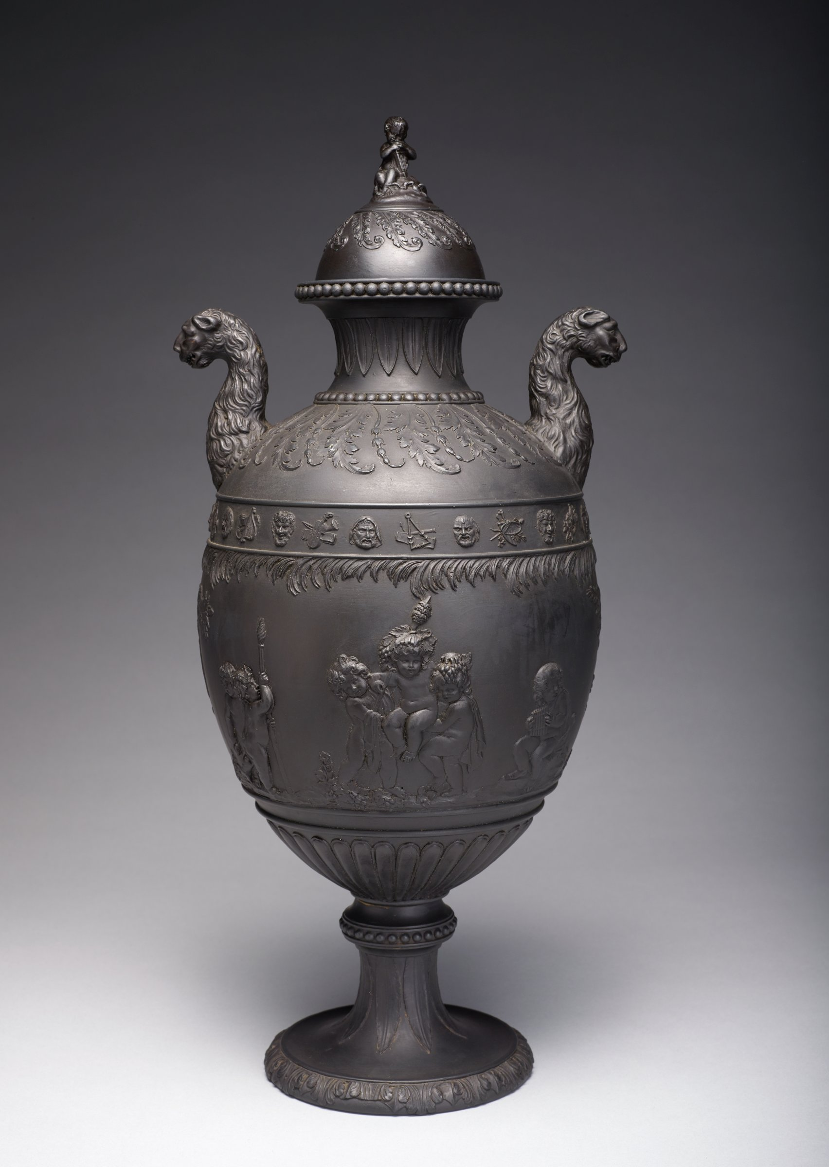 Tall covered urn of black basalt on round foot, the edge with a band of acanthus leaf motifs, the stem with a pattern of stiff leaf elements and with a beaded waist, the lower body with gadrooning and the main body with a scene of Bacchanalian Boys in relief after Lady Diana Beauclerk, including on one side a satyr putti sitting on rocks eating grapes, another sitting under a tree holding a staff, one putti sitting under a tree and dozing and one kneeling with a basket of bunches of grapes, on the other side two putti with a staff, two carrying a third in their arms, and one seated on a rock with pan pipes, trees divide the two sides, above the main body is a band of feathery floral motifs and at the shoulder a band of masks, two of which are Bacchus, and symbols of the arts and sciences, the shoulder with stylized leafy fronds and floral drops, with beading around the neck and lip, stiff leaf motifs on the neck, and two intricate lion, or leopard, handles, the corresponding cover with leafy fronds and a finial in the form of a seated, draped putti with an instrument.