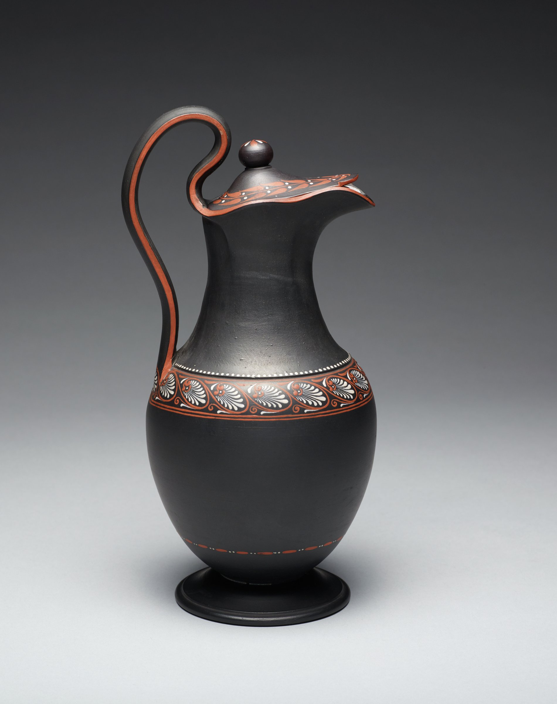 Large covered ewer (formally classified as a chocolate or coffee pot) of black basalt, with bulbous body on plain round foot with a band of dots and dashes at the lower body, at the shoulder a band of stylized anthemion motifs in red and white below a band of small white dots, with long neck and beak spout, curved handle edged in red, the conforming cover with red leafy motifs with white berries and ball finial, the interior glazed.