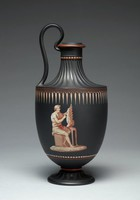 """Jug of black basalt with encaustic painting, derived from the Greek """"oenochoe"""" form, the foot and body above the shoulder and neck are engine turned, the main body with an image of Daedalus building his wings below a tear drop border that extends around the body below the shoulder, with red trim around the lip and stem and a band of beading around the upper neck."""