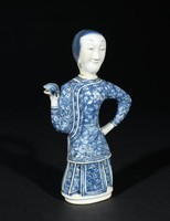 Teapot in the shape of a female figure; the cover is her head