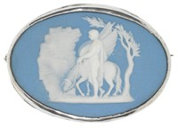 Small oval medallion of solid blue jasper with white bas relief of Bellerophon watering Pegasus below Parnassus – Pegasus, the winged horse, led by Bellerophon bows his head in drink before attacking the three-headed monster Chimaera – set in a simple silver mount with horizontal pin on reverse.