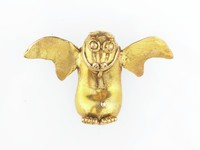Pendant in form of a bat created with open back casting technique with core extracted. Figure has outstretched, bifurcated wings, small erect pointed ears, round protruding eyes, long, flat snout with curled nostrils; smiling, open, fanged mouth with long tongue unfurled onto abdomen; feet at bottom of figure, each with four curled claws. Narrow loop of gold across back for suspension of pendant.