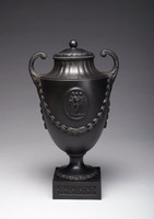 Vase of black basalt on thick, square plinth decorated with bands of palmettes, with round foot with band of overlapping acanthus leaves, the otherwise plain, urn-shaped body with exaggerated leafy garlands with clusters of berries where they meet, in the center on one side a molded medallion with the Three Graces, with two pistol handles that terminate in leafy spreads, the neck and shoulder fluted and with a band of beading around the lip, the cover a facsimile.