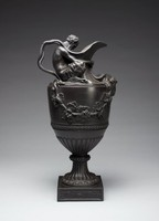 """Large, heavy ewer commonly known as """"Sacred to Bacchus"""" resting on a square plinth with molded scrolling vines, the foot and lower body fluted and with bands of acanthus leaves around the foot and overlapping leaves around the middle of the body, with a smaller band of beading on the stem, the main body with garlands of leafy grape vines and bunches of grapes, on the should of the ewer sits a faun with his head bowed, he holds the horns of a ram in his hands as reins, his arms encompass the neck of the ewer, with a crossed double handle behind him."""