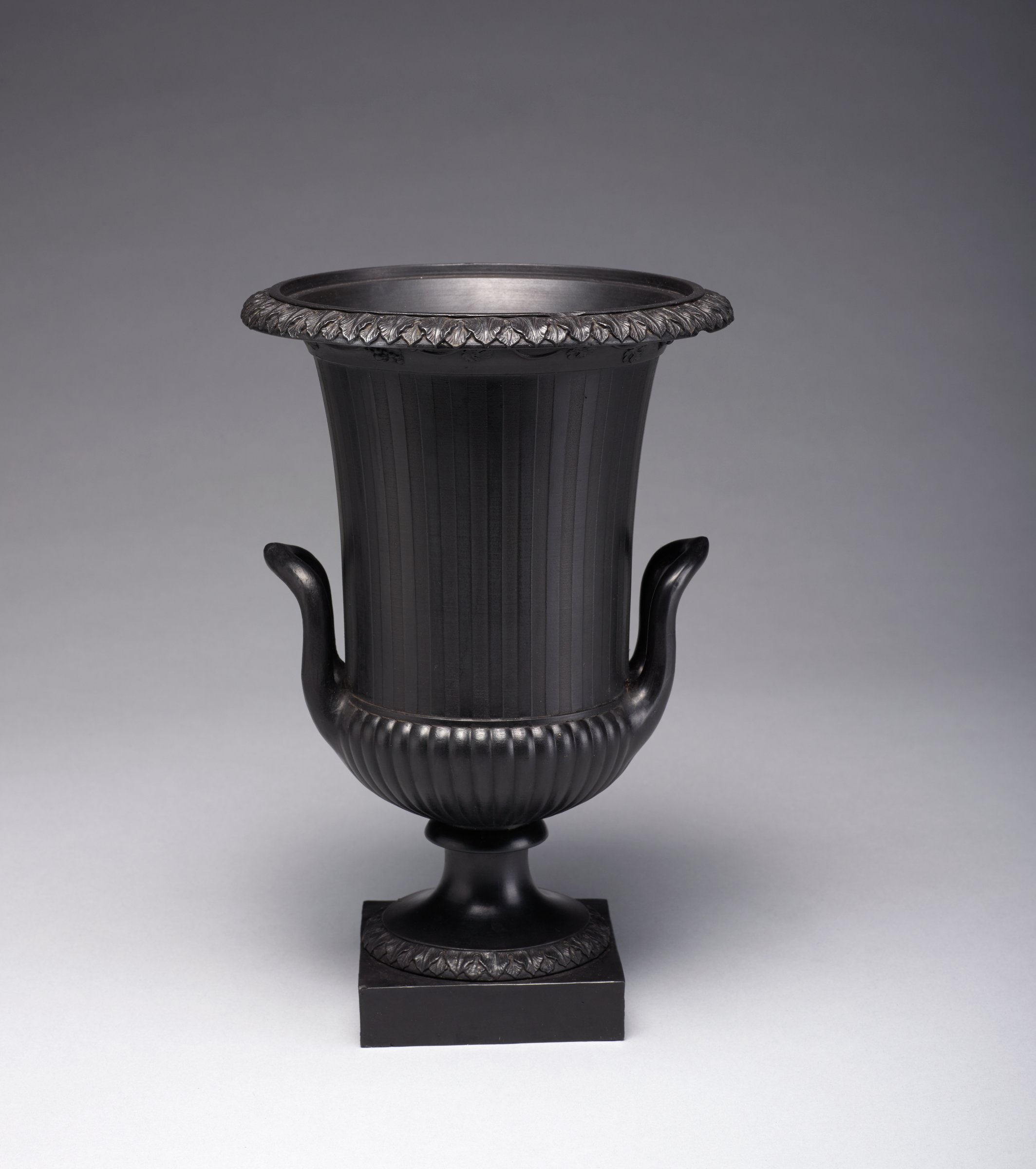 Campana vase of black basalt on small square plinth, the foot with a band of overlapping leaves, the lower body gadrooned and the upper body engine turned, with a band of overlapping acanthus leaves around the flared lip and on the underside of the lip a band of grape leaves and bunches of grapes on a vine, with two short loop handles, the cover missing.