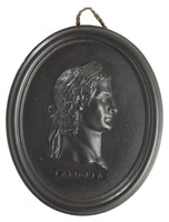 Oval medallion of black basalt with bas relief portrait bust of Roman Emperor Caligula (12-41 AD) facing right, wearing laurel leaf crown, the name CALIGULA impressed below the truncation, self frame, pierced to hang.