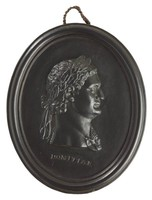 Oval medallion of black basalt with the bas relief portrait bust of Roman Emperor Domitian (51-96 AD) facing right, wearing laurel leaf crown, the name DOMITIAN impressed below the truncation, self frame, pierced to hang.