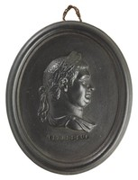 Oval medallion of black basalt with the bas relief portrait bust of Roman Emperor Vitellius (15-69 AD) facing right, wearing laurel leaf crown, the name VITELLIUS impressed below the truncation, self frame, pierced to hang.