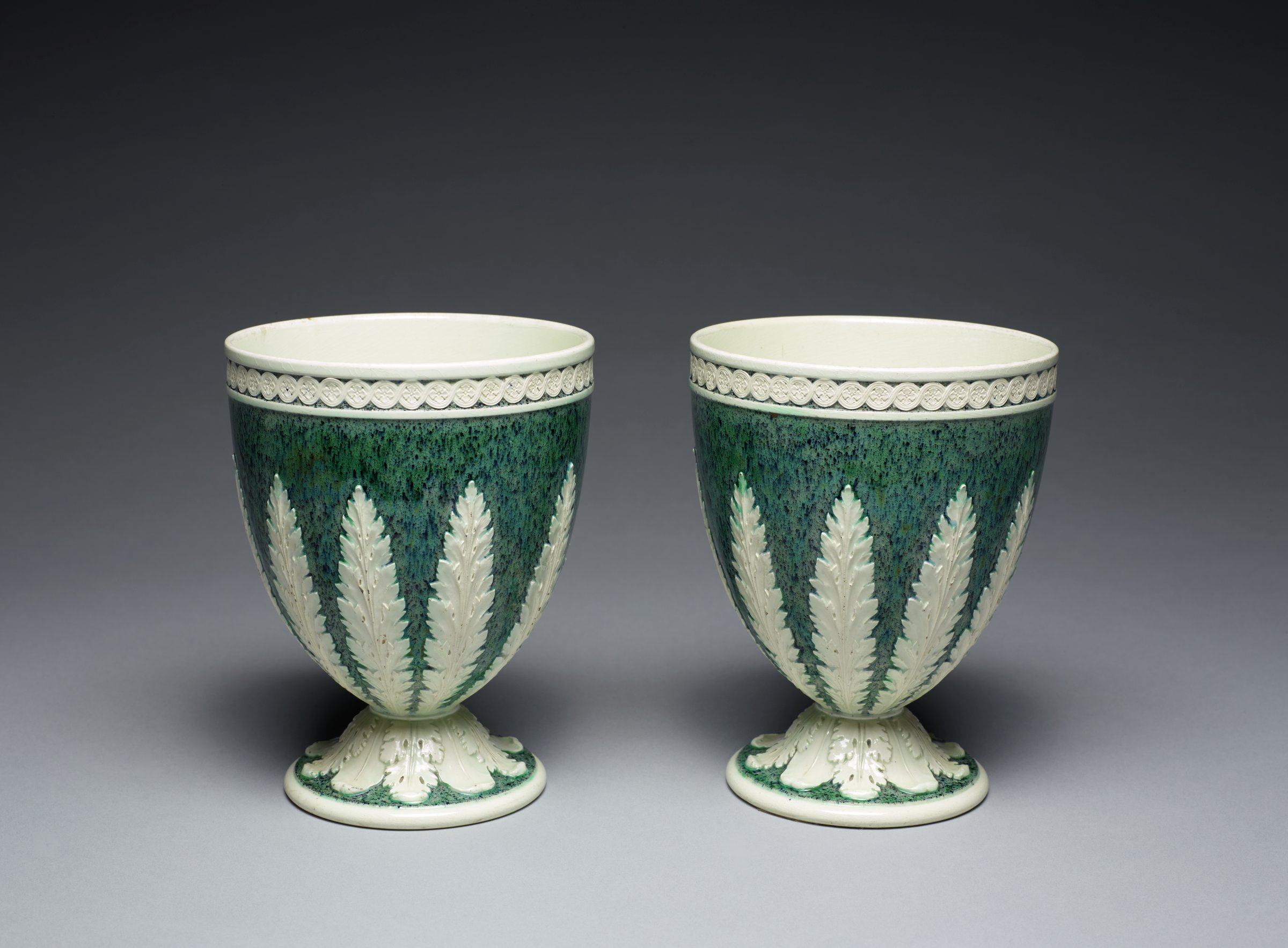 Pair of goblet-shaped vases of white stoneware, the exteriors covered with a green variegated glaze, the body of each with applied, white stiff leaf motifs and overlapping acanthus leaves around the foot, with a band of applied, white repeating medallion motifs below the lip, the interiors white.