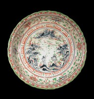 Glazed stoneware dish with figures in a landscape surrounded by a band of scalloped lotus petals and a diaper pattern on a scalloped rim, all painted in underglaze cobalt oxide and enamel colors.