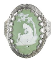 Oval medallion of white jasper with green dip and white bas relief of Poor Maria – a young woman seated under a tree, weeping, with a small dog – mounted in a steel bracelet, the medallion held to the face with prongs, the surrounding border engraved with crosshatching and on either side a simple flower with leafy motifs, the band is attached to the face with hinges and is engraved with a stippled border and on either side a triangle with similar leafy motifs, with adjustable hook and chain clasp.