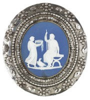"""Small round medallion of white jasper with dark blue jasper dip and white bas relief of an """"Offering to Jupiter"""" — Jupiter is seated on a stool with a staff and an eagle by his side, a young maiden approaches him with a large round bowl — in a cut-steel mount set with two bands of faceted cut-steel beads and a wider band of small cut-steel beads arranged in a floral pattern between single, larger, oval, faceted cut-steel beads, the reverse with a brass and steel pin (a later addtion or repair)"""