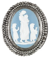 Oval buckle comprised of a solid light blue jasper medallion with white jasper bas relief of Domestic Employment – a young woman holding an infant with a small child walking in front and another behind her, set in a cut steel mount with two rows of beading