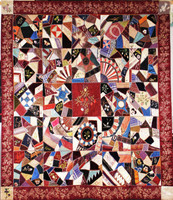 """Very opulent crazy quilt of silk, velvet and satin, in the center a large burgundy-colored square with a bouquet of silk embroidered flowers framed by four fans of fabric and embroidery, most of the patches are heavily embroidered, some are painted, a wide satin border embroidered with a strawberry vine, with a faded ribbon with """"Grand Commandery State of Iowa"""" and dated 1883."""