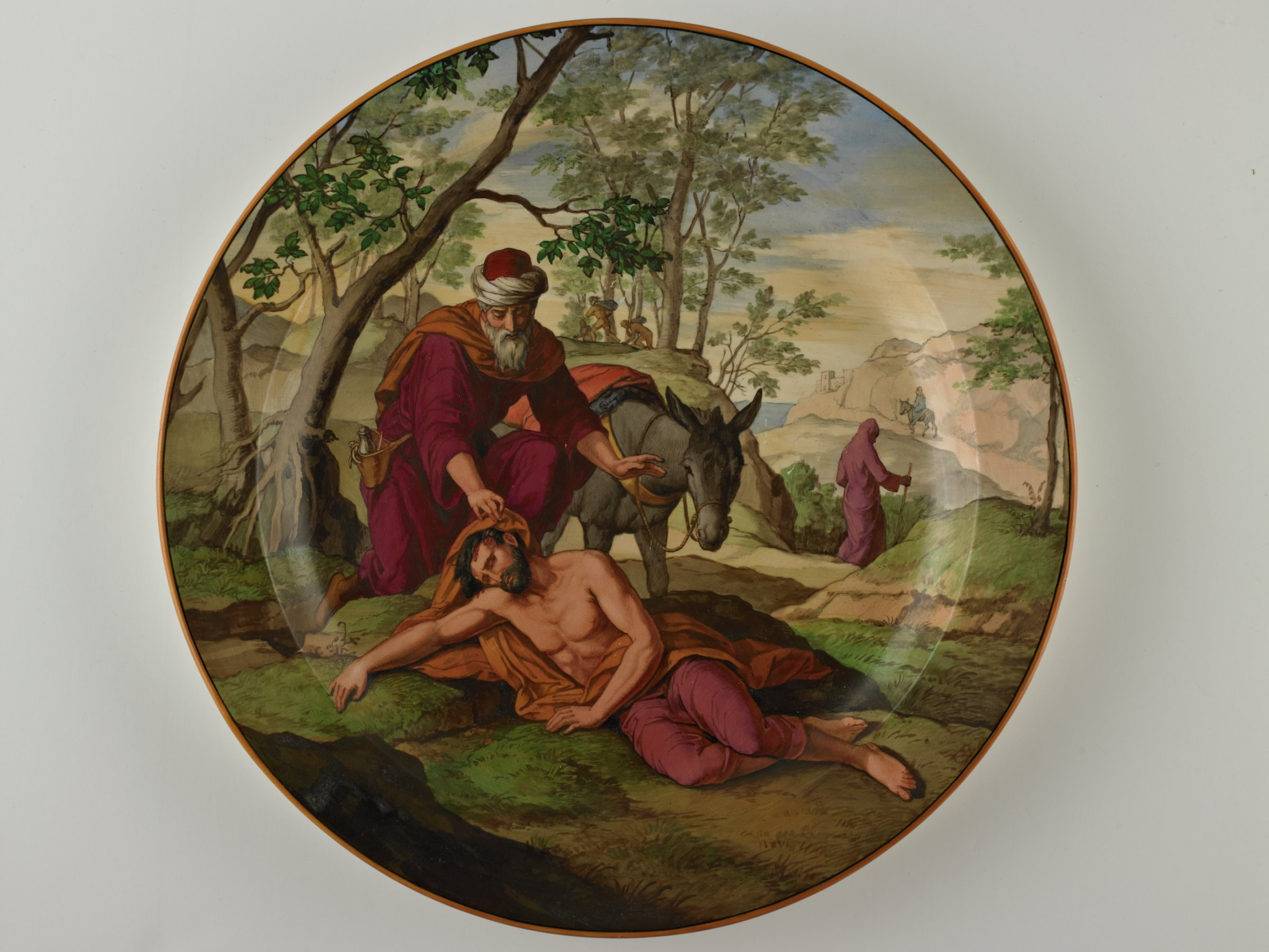 Large plate of creamware with shallow well and wide rim, painted on the front with the scene of the Good Samaritan - in a landscape a man lies unconscious on the road in the foreground while a man with a donkey stops to help, further along the road a cloaked figure with a walking stick walks away, the plate with a mustard-yellow edge.