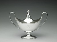 One of a pair of silver, boat-shaped, covered sauceboats, each raised on stepped oval foot with beaded edge, the upper rim of the main body likewise beaded, with two large, loop handles with reeded accents, the fitted, domed cover notched to accommodate a ladle, with beaded urn finial, both the cover and the body on one side engraved with a stag crest.