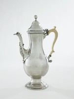Tall, plain silver coffeepot of elongated pear shape on splayed and stepped round foot, with modestly curved spout with acanthus leaf accents, the bone handle double scrolled with silver terminal and small curved thumb rest, the hinged, domed lid with large ball finial.